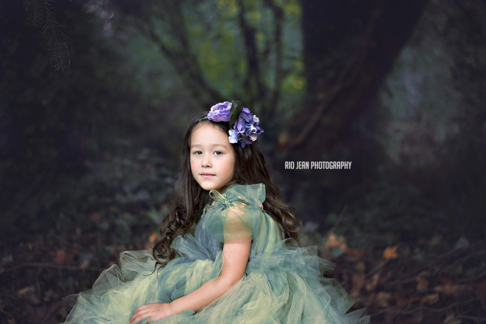 little-girl-in-green-tulle-dress-sitting-on-a-rock-with-a-purple-headpiece